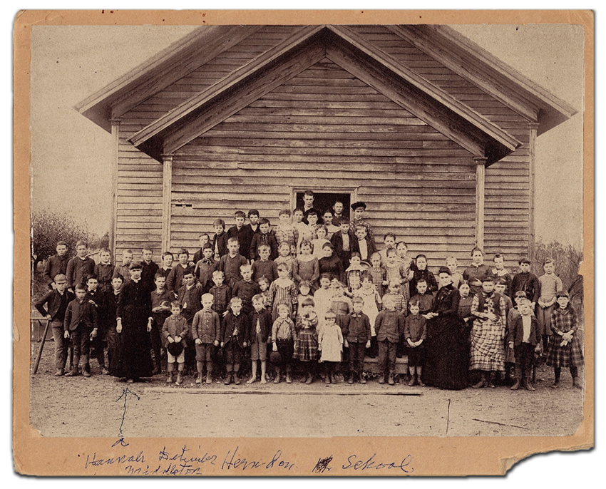 Black and white photograph of the first Herndon public school. Two teachers and approximately 70 children are pictured in front of a single-room, single story frame school building.