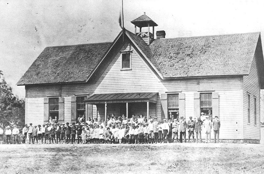 Black and white photograph of the three-room Herndon School. The building has been enlarged substantially. A large group of students is pictures standing in front of the school.
