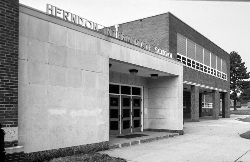 Black and white photograph of the main entrance of Herndon Intermediate School.